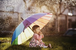 little happy girl with a rainbow umbrella in park